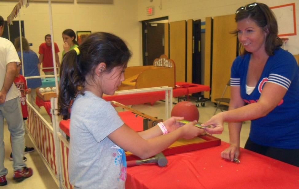 Volunteer handing a girl tickets at fundraising event